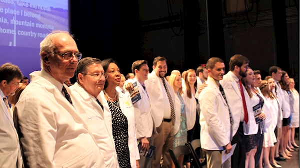 Class of 2022 joins in singing Country Roads at the end of the clinic induction or white coat ceremony