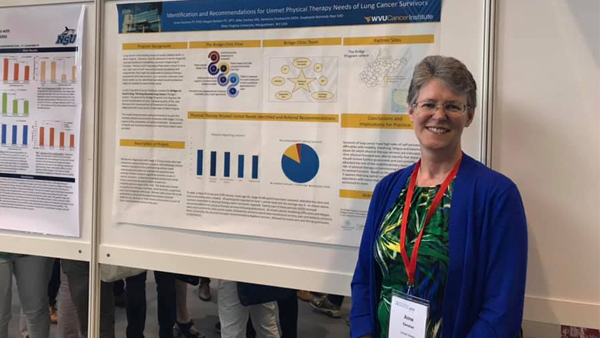 Dr. Anne Swisher standing in front of her poster at a conference in Geneva Switzerland in May, 2019.