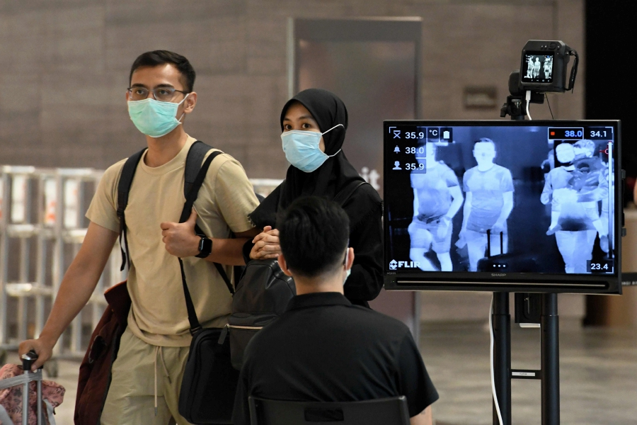 Travelers walk by a thermal image camera in Singapore. Photo AFP.