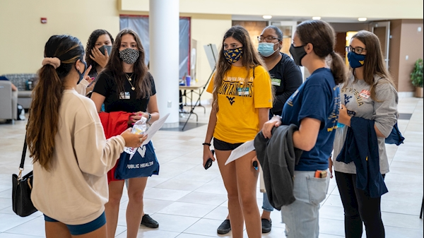 group of maksed students stand in the Pylons area of the Health Sciences Center during their tour