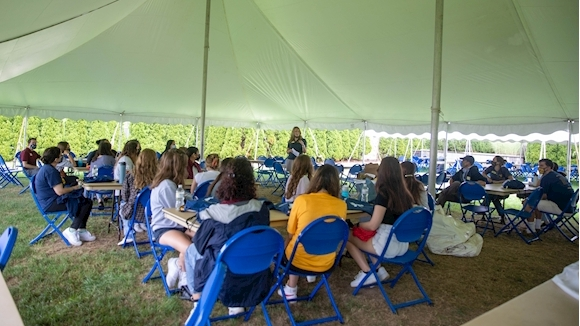Undergraduate students sit outside under a tent as Audra Hamrick welcomes them to the event on Aug. 16