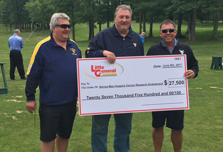 WVU Basketball Coach Bob Huggins is presented a check for $27,500 by Greg Darby and Cory Beasley.
