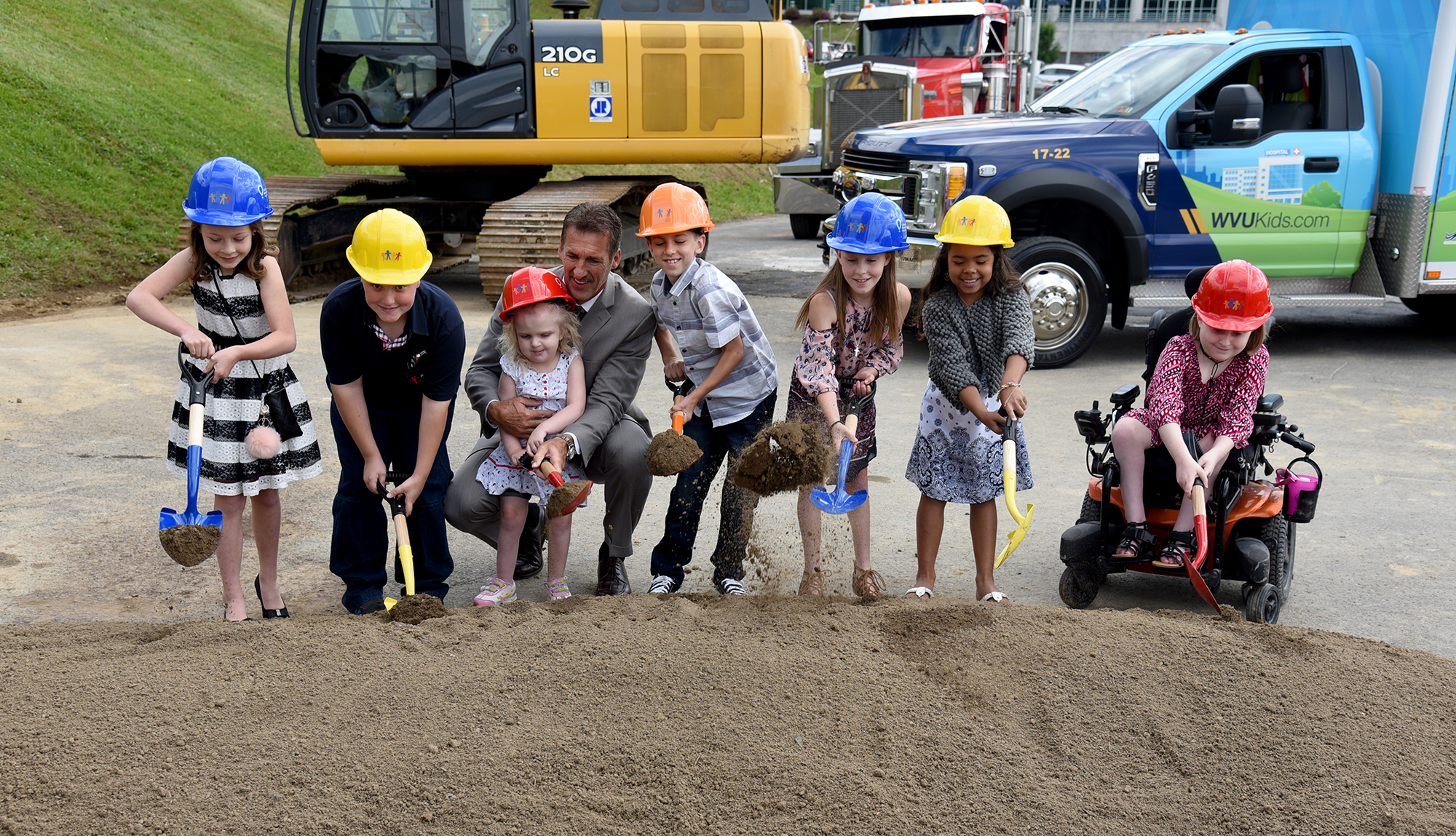 Current and former patients shoveling dirt to break ground for the new WVU Medicine Children's
