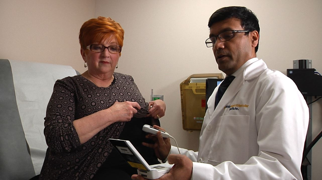 Dr. Partho Sengupta explains portable ultrasound technology to a patient in the SMART clinic