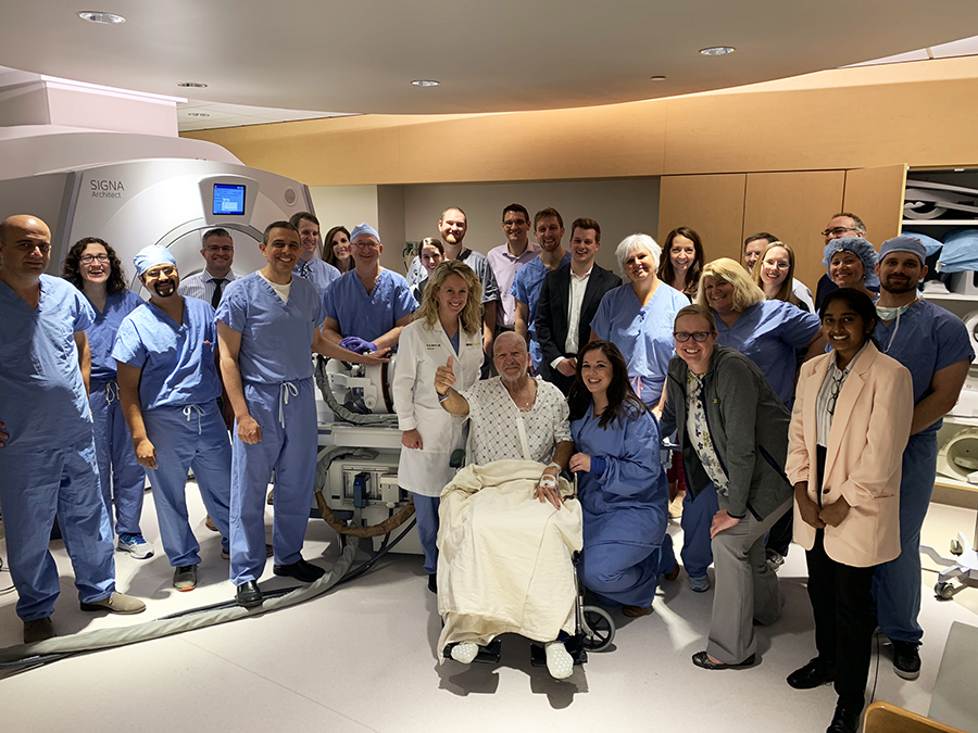 Don Wahl (seated) gives a thumb's up after undergoing MR-guided focused ultrasound for essential tremor at the WVU Rockefeller Neuroscience Institute. He is pictured with the team that performed the procedure.