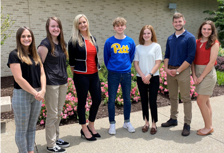 Caitlin Cowell, Aryon Marshall,  Ashley Eby, Lev Ivanov, Brianne Falatovich, Adam Bobak,  Morgan Glass stand in a group in front of the WVU HSC Learning Center building.