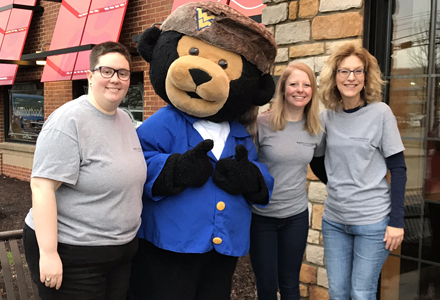 Cancer Institute Care team pose with Monti Bear mascot at annual pancake fundraiser.