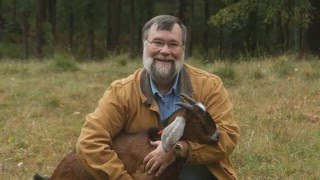 Larry Rhodes in field holding a goat