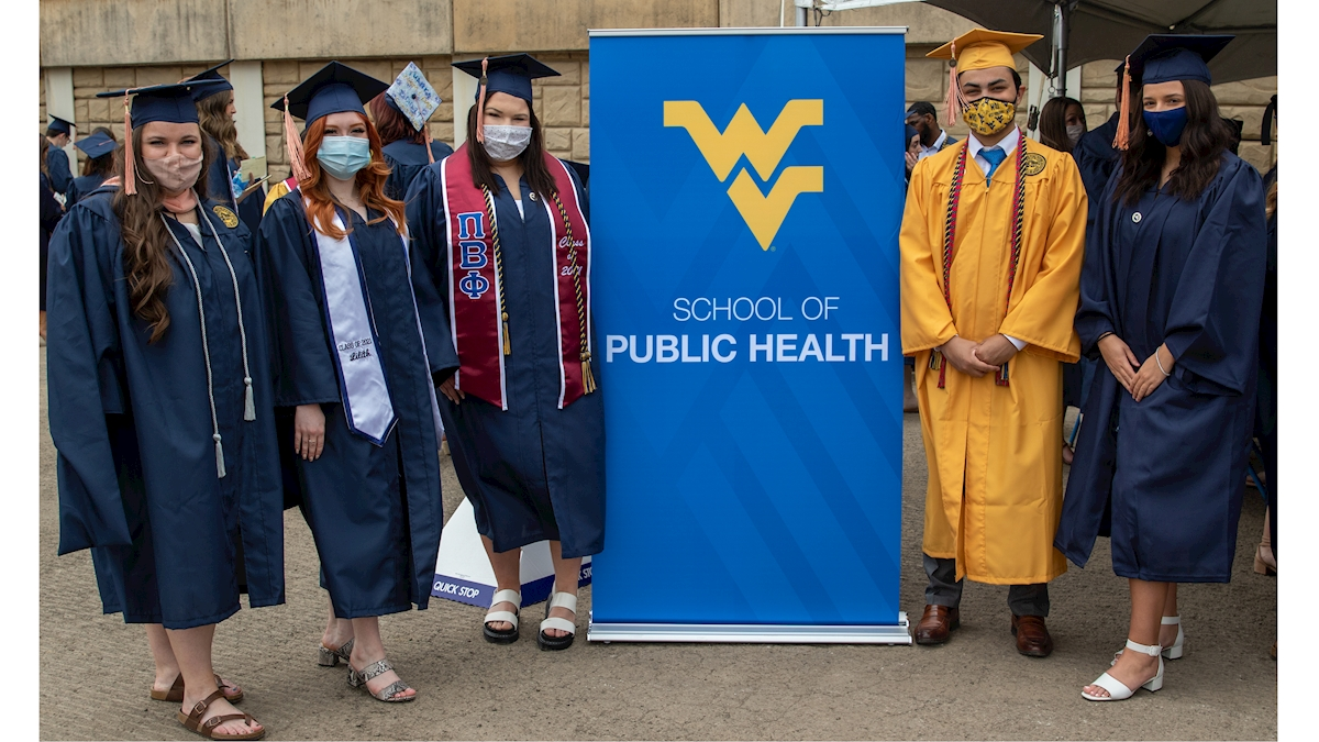 Chrissy Donahue, Lilith McGhee, Dakota McCollian, Jeevan Murthy and Adrian Thomas donning their graduation caps and gowns as they stand beside a School of Public Health vertical banner.