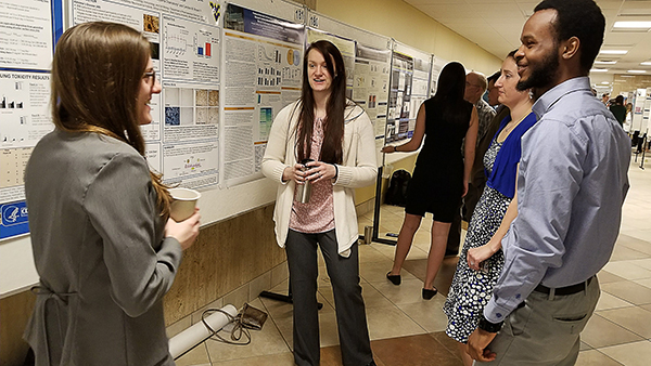 Hannah Wilson, presents her poster to a group of colleagues at the 2018 Van Liere poster competition.