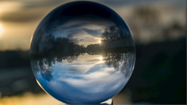 A mirror reflects light in a scenic river shot.