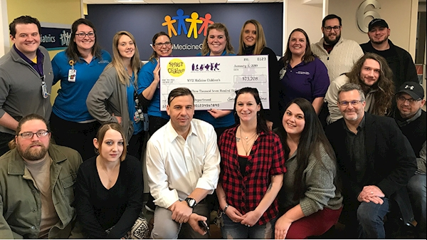 The WVU Medicine Children's Child Life Team, including (standing, left to right) Stephen Surgener, Lauren Musinski, Kaitlin Travinski, Evy Wright, Jill Noha, Christine Haufe, and Bridget Ullery, accepts a $73,708 donation from area representatives of the Spirit Halloween Spirit of Children program.