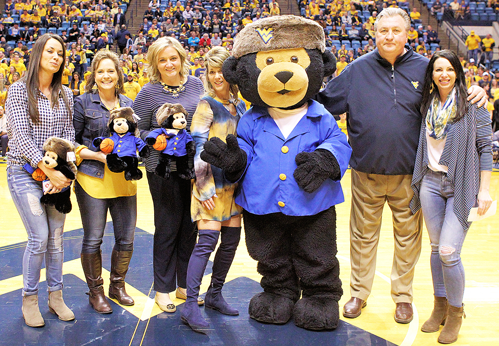 WVU Men's Basketball Coach Bob Huggins (second from right) receives a check for the Norma Mae Huggins Cancer Research Fund from (left to right) Kerry Gibson, former member of the Friends of WVU Hospitals Board of Directors; Stacie Redelman, current president of the Friends of WVU Hospitals Board of Directors; Whitney Rae Hatcher, manager of Volunteer Services and Friends Gift Shop; Stacy Shearer, former vice president of the Friends of WVU Hospitals Board of Directors; Monti Bear; and Victoria Shuman, former president of the Friends of WVU Hospitals Board of Directors.