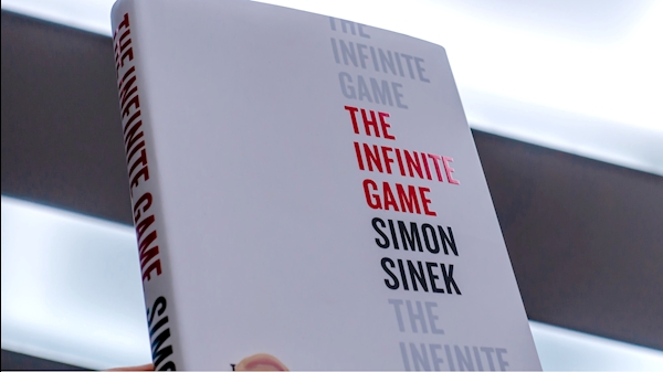 "Simon Snek's book cover held up, ""The Infinite Game."""