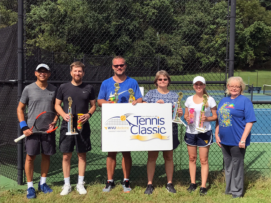 Winners of the 2018 WVU Medicine Frank Sabado, Jr, MD Tennis Classic are pictured from left to right with tournament officials:  Tournament Co-Chair Ernie Agbayani, M.D., Men's Champion Brian Romine, Men's Finalist/Most Aces Scott Smith, Women's Finalist Amy Rush, Women's Champion Katelyn Mumaw, and Retha Sabado.
