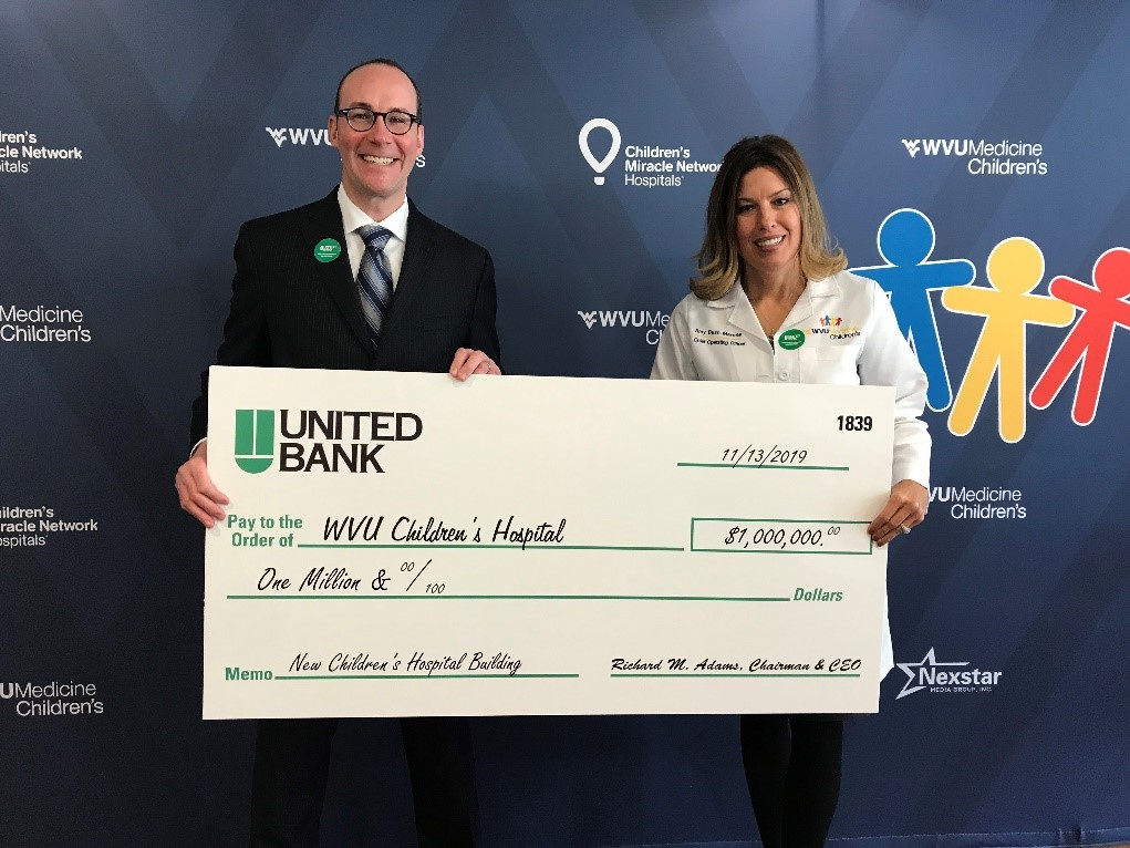 Albert L. Wright Jr., president and CEO of the West Virginia University Health System, and Amy L. Bush-Marone, chief operating officer at WVU Medicine Children's, pose with a $1 million check presented Wednesday, Nov. 13, by United Bank for the new WVU Medicine Children's tower.