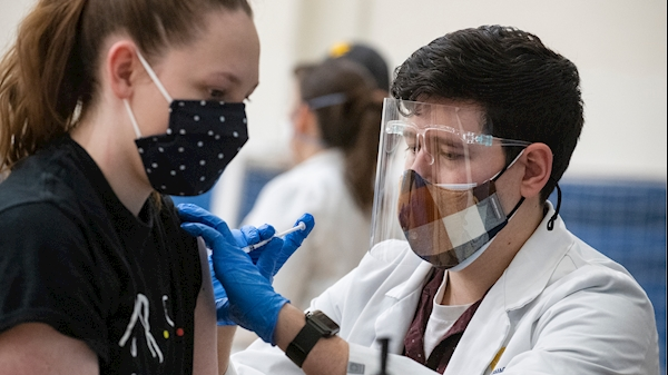 A WVU student pharmacist (right) administers a COVID-19 vaccine to a Health Sciences clinical student (left)