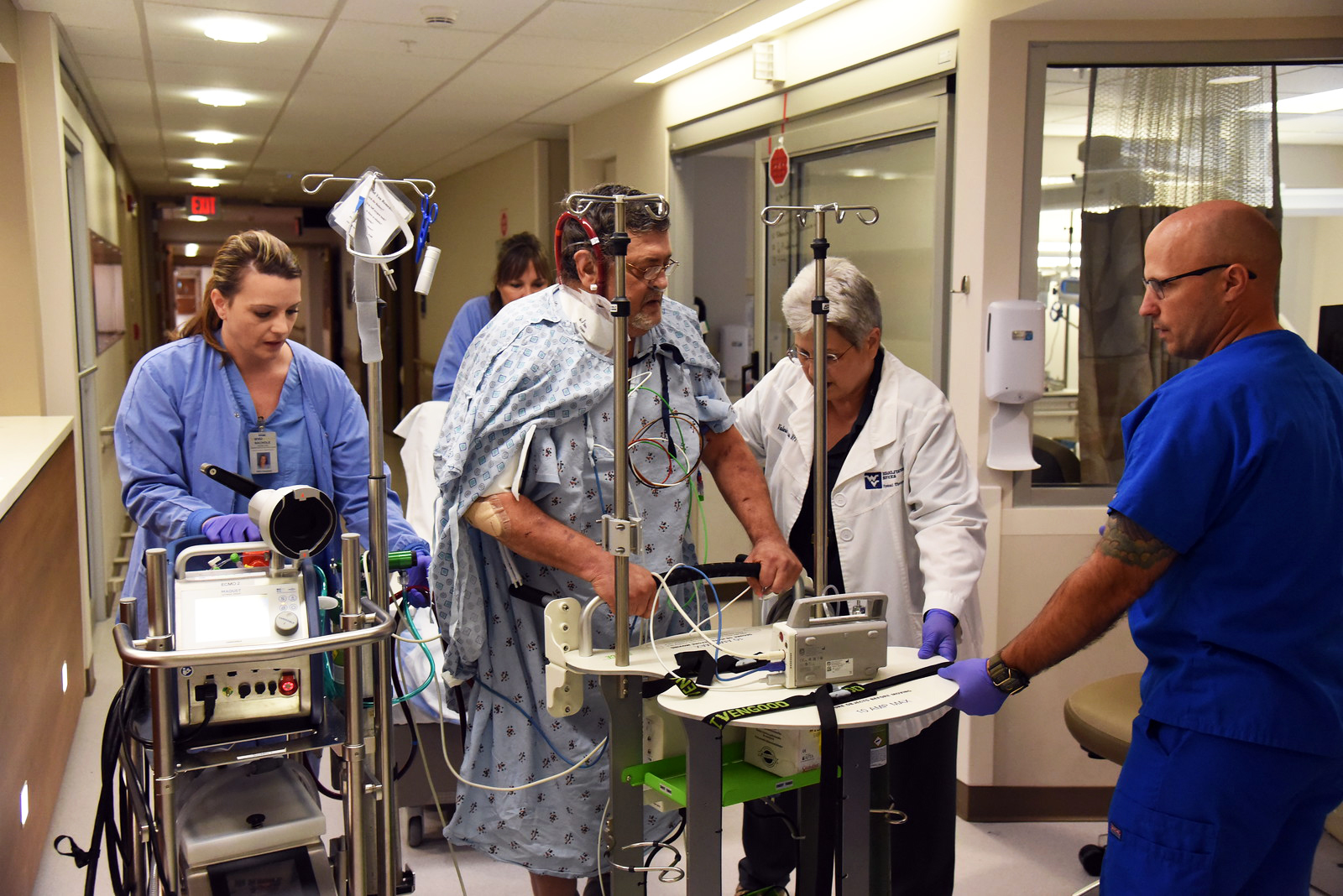 ECMO patient Charles Shoffler walks with the assistance of nurses and therapists