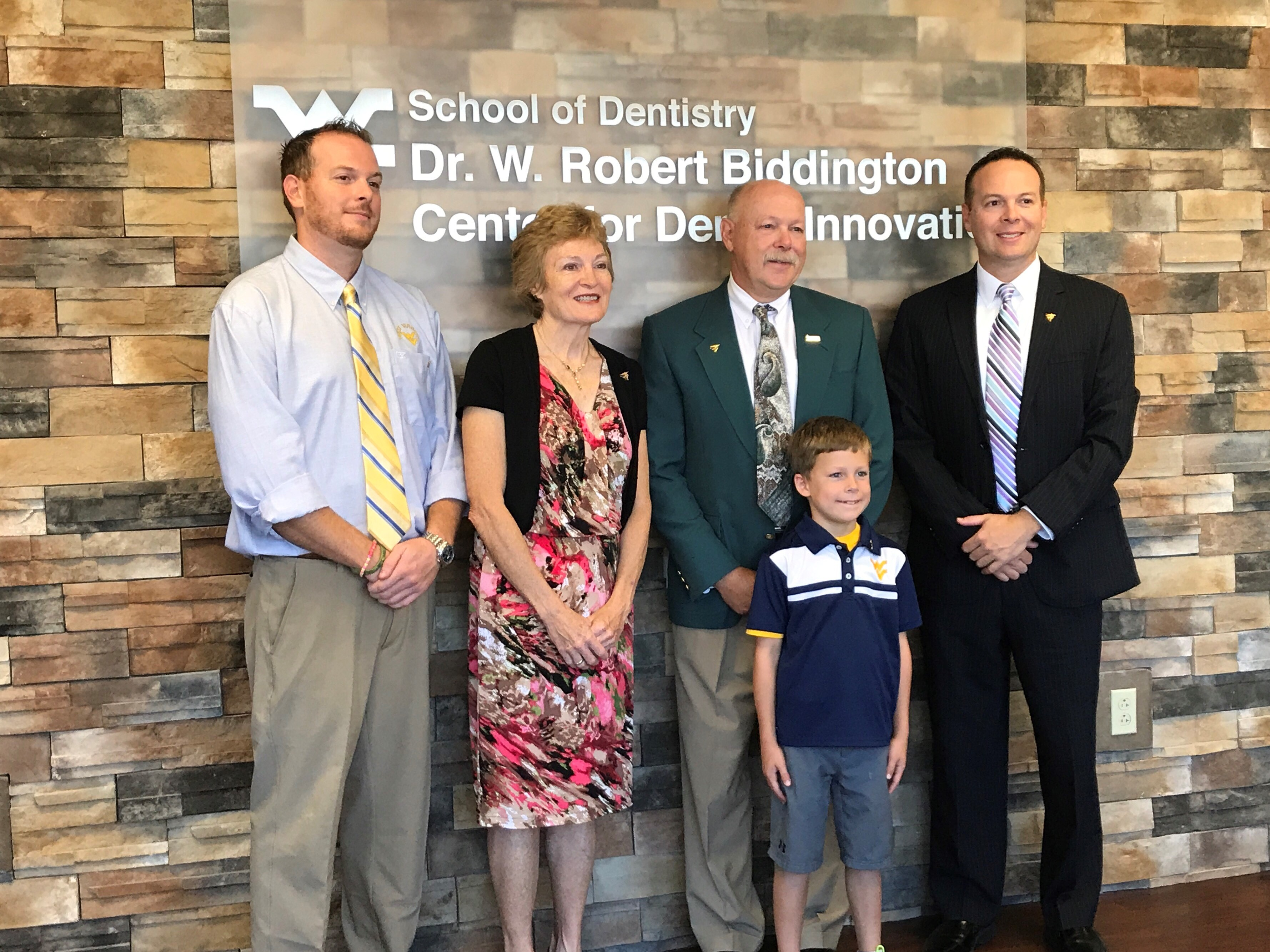 The family of Dr. W. Robert Biddington pose for a photo in front of the innovation center sign bearing the longest serving dean's name.