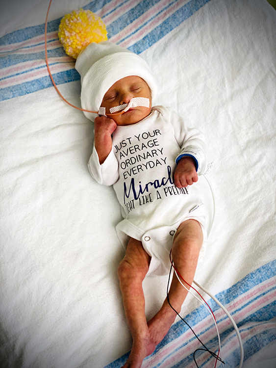 """Emily May Resh, daughter of Jessica Resh and Jerry Bennett of Cumberland, Maryland, was born at 34 weeks gestation. She is pictured wearing a onesie that says, """"Just your average ordinary everyday miracle. Fight like a preemie"""" in honor of Prematurity Awareness Month."""