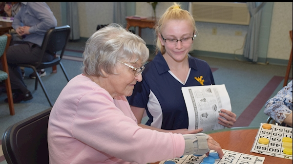 WVU student pharmacist Haley Saville (right) works with Sundale resident Evelyn Anderson