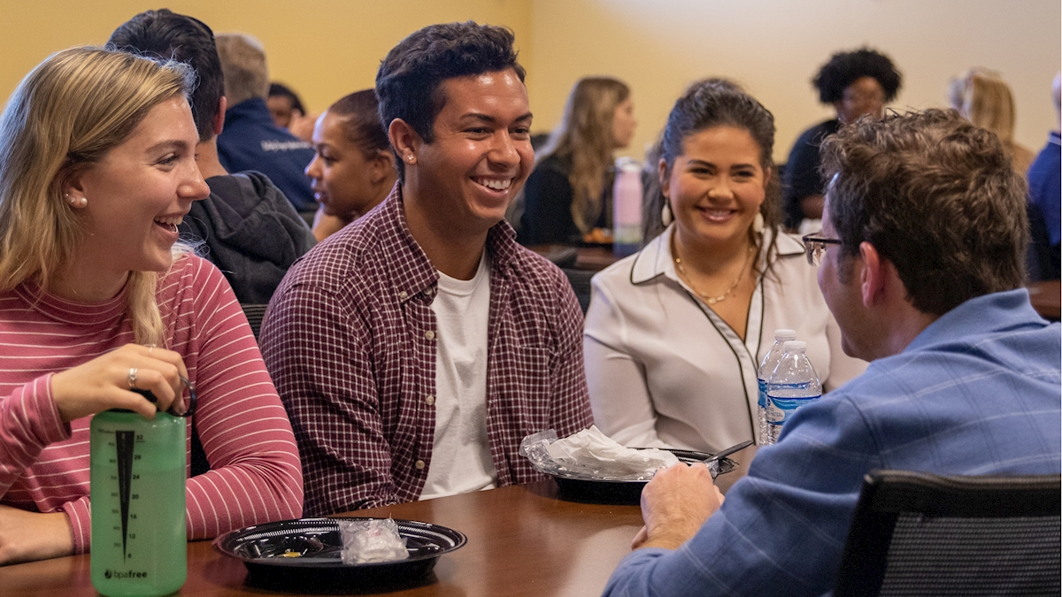 three students sit with a professor during the fall 2019 research networking event