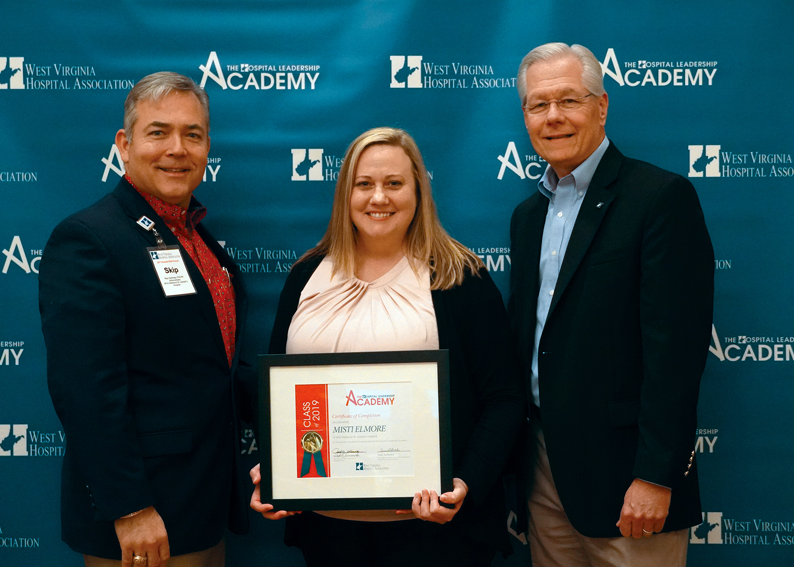 Skip Gjolberg, president of St. Joseph's Hospital (left), and Joseph Letnaunchyn, president and CEO of the West Virginia Hospital Association (right), present Misti Elmore with her certification of completion.